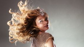 Mysterious enigmatic attractive woman girl. Mysterious enigmatic woman in studio on grey. Young intriguing attractive girl with flying long curly hair in motion Stock Photography