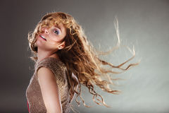 Mysterious enigmatic attractive woman girl. Mysterious enigmatic woman in studio on grey. Young intriguing attractive girl with flying long curly hair in motion Royalty Free Stock Photography
