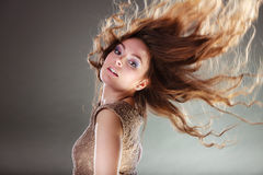 Mysterious enigmatic attractive woman girl. Mysterious enigmatic woman in studio on grey. Young intriguing attractive girl with flying long curly hair in motion Stock Images
