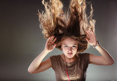 Mysterious enigmatic woman girl with flying hair. Portrait of mysterious enigmatic woman in studio on grey. Young intriguing attractive girl with flying hair in Stock Photography