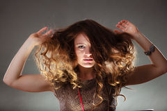 Mysterious enigmatic woman girl with flying hair. Portrait of mysterious enigmatic woman in studio on grey. Young intriguing attractive girl with flying hair in Stock Images