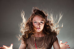 Mysterious enigmatic woman girl with flying hair. Portrait of mysterious enigmatic woman in studio on grey. Young intriguing attractive girl with flying hair in Stock Photos
