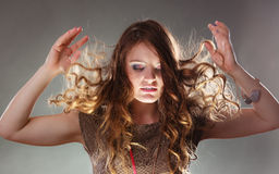 Mysterious enigmatic woman girl with flying hair. Portrait of mysterious enigmatic woman in studio on grey. Young intriguing attractive girl with flying hair in Royalty Free Stock Photos