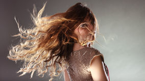 Mysterious enigmatic woman girl with flying hair. Portrait of mysterious enigmatic woman. Young intriguing attractive girl with flying hair in motion. Shining Stock Image