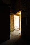 Mysterious entrance. Sunlight breaks into an open door, setting a mysterious mood.  Scene is found at an abandoned army fort in the Boston Harbor islands Stock Image