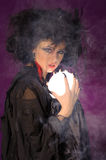 Mysterious fashion witch. Mysterious fortune telling woman with glowing crystal ball looking at the camera Royalty Free Stock Images