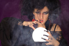Mysterious fashion witch. Mysterious fortune telling woman with glowing crystal ball looking at the camera stock photos
