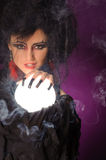 Mysterious fashion witch. Mysterious fortune telling woman with glowing crystal ball looking at the camera Stock Photo