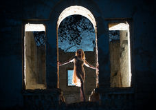 Mysterious female figure. Mysterious female silhouette in the arc of the ruined building Royalty Free Stock Photos