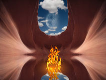 Mysterious Flame. Mysterious fire burns on still waters surface in desert cave Royalty Free Stock Image