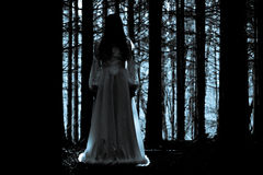 Mysterious girl in dark spooky forest