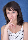 Mysterious girl with a finger near lips Stock Photo