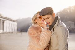 Mysterious girl is telling tender words to her boyfriend. Tell me your secrets. Pleasant loving positive smiling couple is standing on street. Young women in stock photography