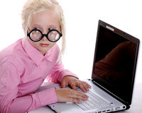 Mysterious Girl Typing on her Laptop in Secrecy. Mysterious little girl implies secrecy typing on her laptop as she looks away to see if onlookers are watching Stock Images