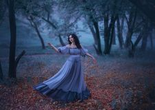 A mysterious girl with wavy dark hair is dancing alone on fallen autumn leaves in a gloomy night forest in a long stock photo