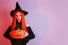 Mysterious halloween costume. Gothic woman magician in hat and red hair in black dress holding jack pumpkin. Magician with red lip royalty free stock image