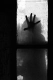 Mysterious hand on a window. Mysterious horrible hand silhouette on a window Royalty Free Stock Image