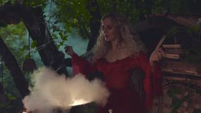 Mysterious woman in magnificent red plate, great sorceress created potion stock footage