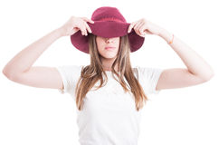 Mysterious hipster wearing casual outfit and hat with large brim. Covering her eyes on white background royalty free stock photo