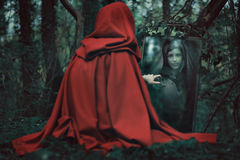 Mysterious hooded woman in front of a magical mirror Stock Images