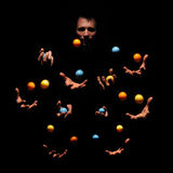 Mysterious juggling man in dark. Ten hands concept. Royalty Free Stock Images