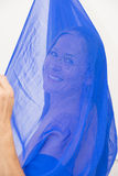 Mysterious lady behind blue scarf Royalty Free Stock Images