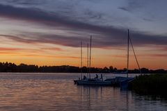 A mysterious landscape with sailing boats after sunset at Kalwa lake. A mysterious landscape after sunset at Lake Kalwa in Masuria in Poland. On the first plan a stock photography