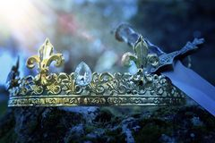 Mysterious and magical photo of silver king crown and sword over the stone covered with moss in the England woods or field. Landscape with light flare. Medieval stock image