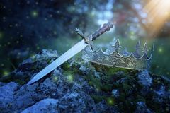 Mysterious and magical photo of silver king crown and sword over the stone in the England woods or field landscape with light. Flare. Medieval period concept stock image
