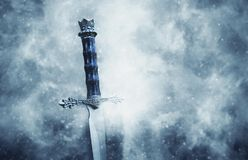 Mysterious and magical photo of silver sword over gothic snowy black background. Medieval period concept. Mysterious and magical photo of silver sword over royalty free stock image