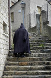 Mysterious Man. A mysterious man wearing a cloak and climbing up the steps with old architecture Stock Image