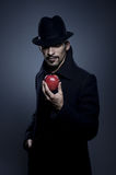 Mysterious man holding an apple stock photo