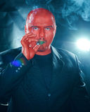 Mysterious man with red face smoking cigar. Royalty Free Stock Image
