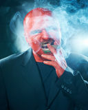 Mysterious man with red face smoking cigar. Royalty Free Stock Photo