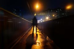 A mysterious man stands alone in the street, among cars in an empty city, weat road after the rain, walks the night street, dreams Royalty Free Stock Photo