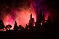 Mysterious medieval castle in a misty full moon. Abandoned gothic style old castle at night. Selective focus royalty free stock images