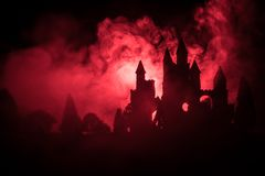 Mysterious medieval castle in a misty full moon. Abandoned gothic style old castle at night. Selective focus stock photography