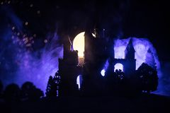 Mysterious medieval castle in a misty full moon. Abandoned gothic style old castle at night. Selective focus royalty free stock photo