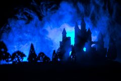 Mysterious medieval castle in a misty full moon. Abandoned gothic style old castle at night. Selective focus stock image