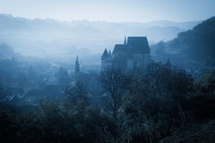 Mysterious misty morning over Biertan village, Transylvania, Romania. Royalty Free Stock Photo
