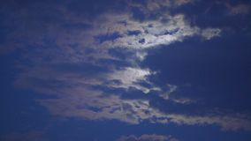 Mysterious moon hiding behind clouds, shining brightly in dark night sky, dreams. Stock footage stock footage