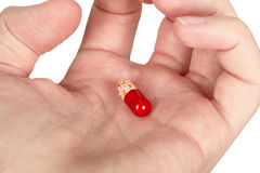 Mysterious multi-colored pill in palm Royalty Free Stock Image