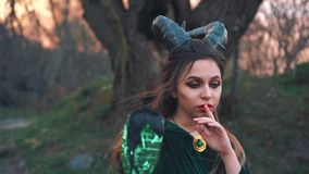 Mysterious mythical creature with large sharp black horns on head holds finger at red bright lips, girl in long green