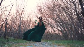Mysterious mythical creature slowly walks through forest with bare trees, lady in long green emerald flying dress with