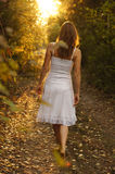 Mysterious path. Young girl with white dress walking onto a mysterious path in the forest Stock Photos