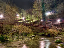 Mysterious path, walkway through woods,over stream. By night wit. Some fog adds to the rather eery atmosphere Stock Images