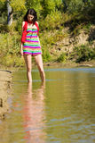 Mysterious pretty girl wanders in the shallow waters Royalty Free Stock Image