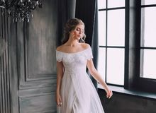 Mysterious pretty lady with blond curly hair looks down modestly, enchanted girl in chic light white long vintage dress royalty free stock photography