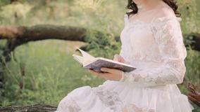 Mysterious princess in a long white vintage light summer dress is reading a book in forest. holding an open notebook in. Her hands. no faces on video. gently stock video