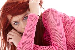 Mysterious redhead in pink fishnet Royalty Free Stock Images